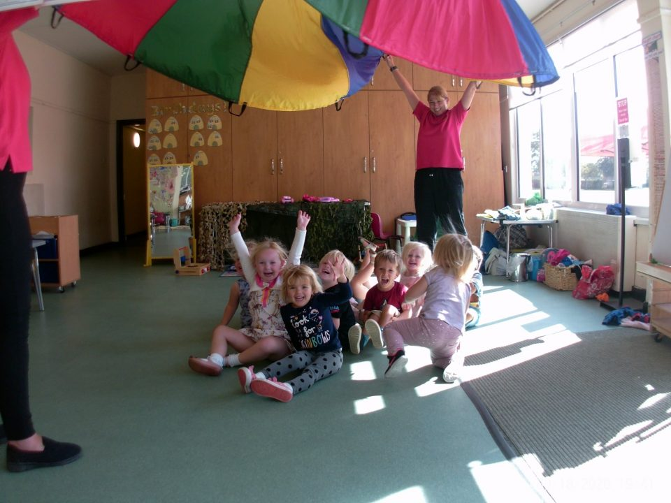 Children laughing whilst playing under a parachute